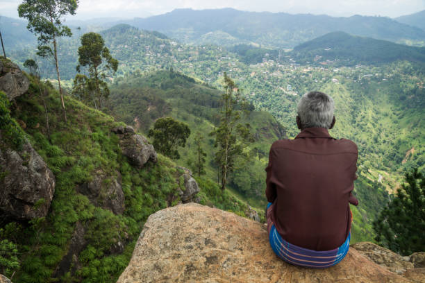 Local man with sarong enjoying the view into the valley of Ella Rock stock photo