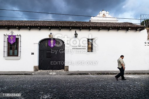 Antigua, Guatamala - 23 March 2018: Local men passing by a colonial style house 'Casa de las Golondrinas' with dramatic cloudcape