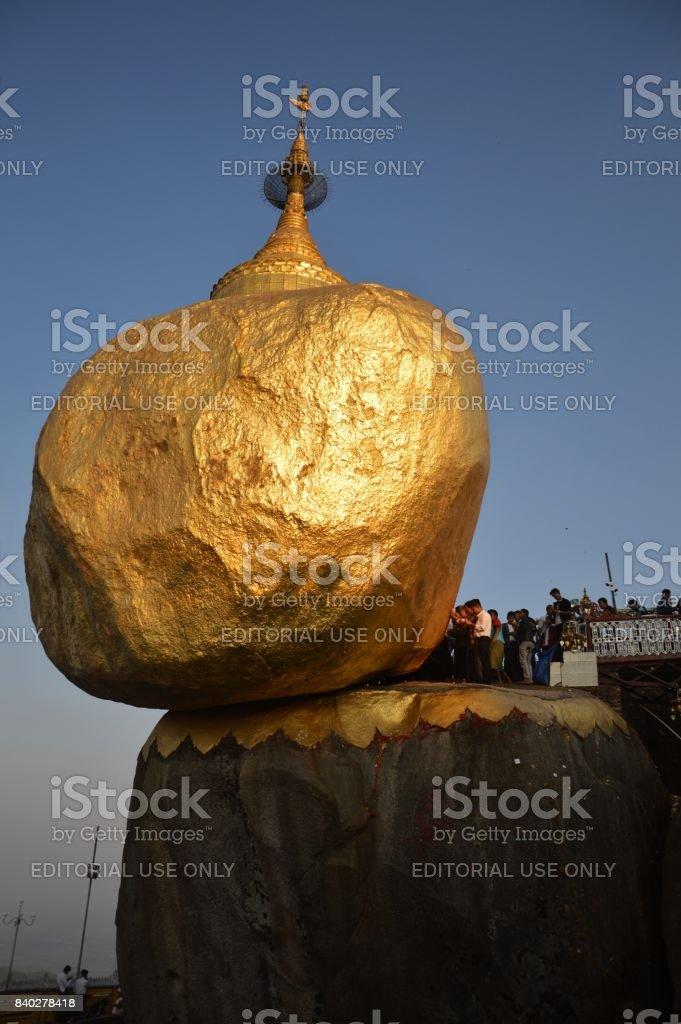 Local men touching Kyaiktiyo Pagoda stock photo