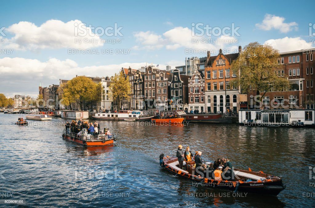 Local people and tourists dressed in orange clothes ride on boats and participate in celebrating King's Day stock photo