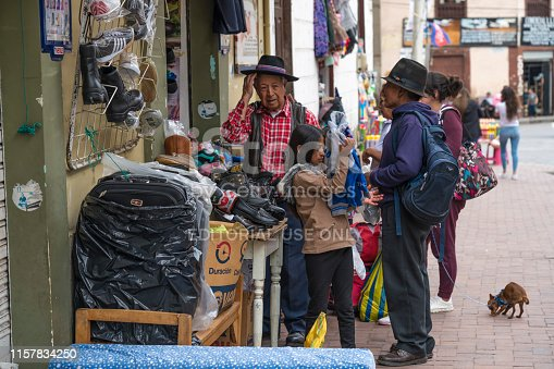 Alausi, Ecuador - March 2, 2019: Local people in every day's activity on the city street in front of a store.   Nariz del Diablo railway station.
