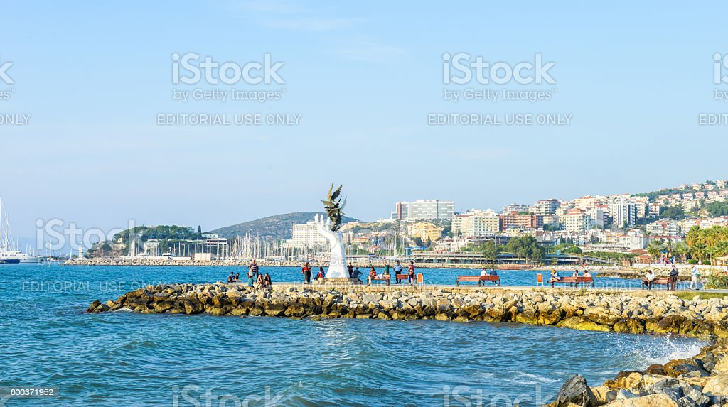 local people enjoying life around signature sculpture at the coastline stock photo