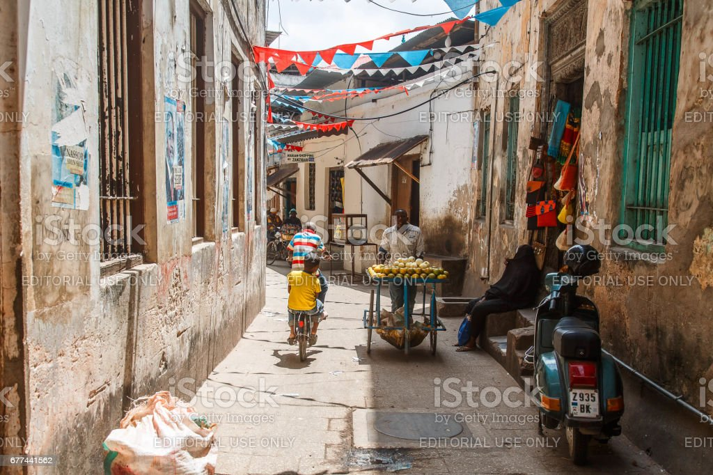 Local people on a street in Stone Town. Stone Town is the old part of Zanzibar City, the capital of Zanzibar, Tanzania stock photo