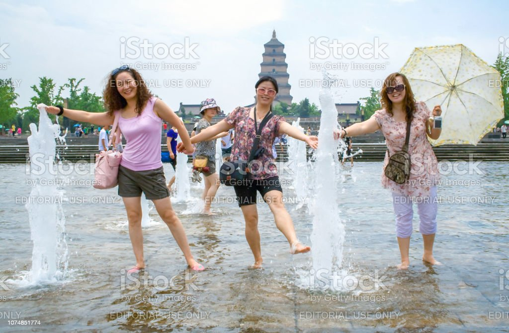 Local people playing with the water during summer in the Music...