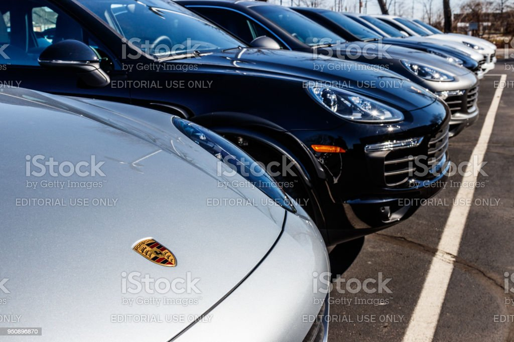 Local Porsche Dealership displaying new SUVs. Porsche Racing dates to the 1950s I Indianapolis - Circa March 2018: Local Porsche Dealership displaying new SUVs. Porsche Racing dates to the 1950s I Car Stock Photo