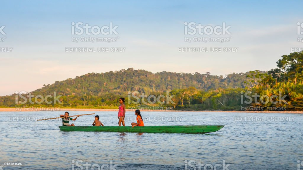 Local Quechua tribe teenagers in the Ecuadorian Amazon on a canoe on the river Napo stock photo