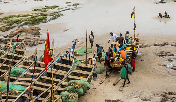 Local residents near the fishing boat in Ghana stock photo