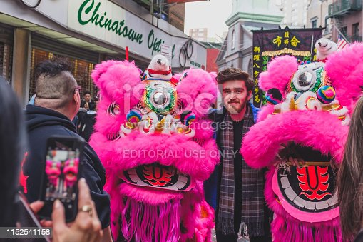 Manhattan, New York, USA - Feb. 5, 2019: A local taking photos with two lion dance performers during a Chinese New Year celebration event in Chinatown