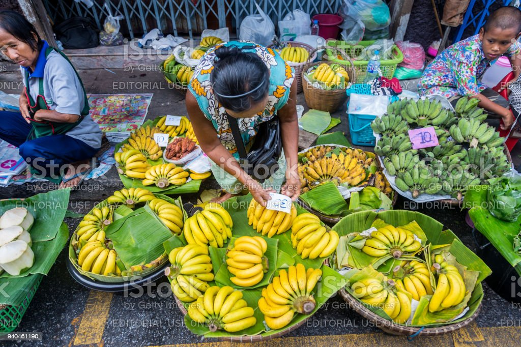 Local Thai woman put price tag down on her bananas at a local fresh market in Phisanulok, Thailand stock photo