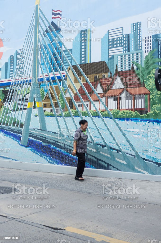 Local Thai woman walking down the empty street with cityscape mosaic behind her. stock photo