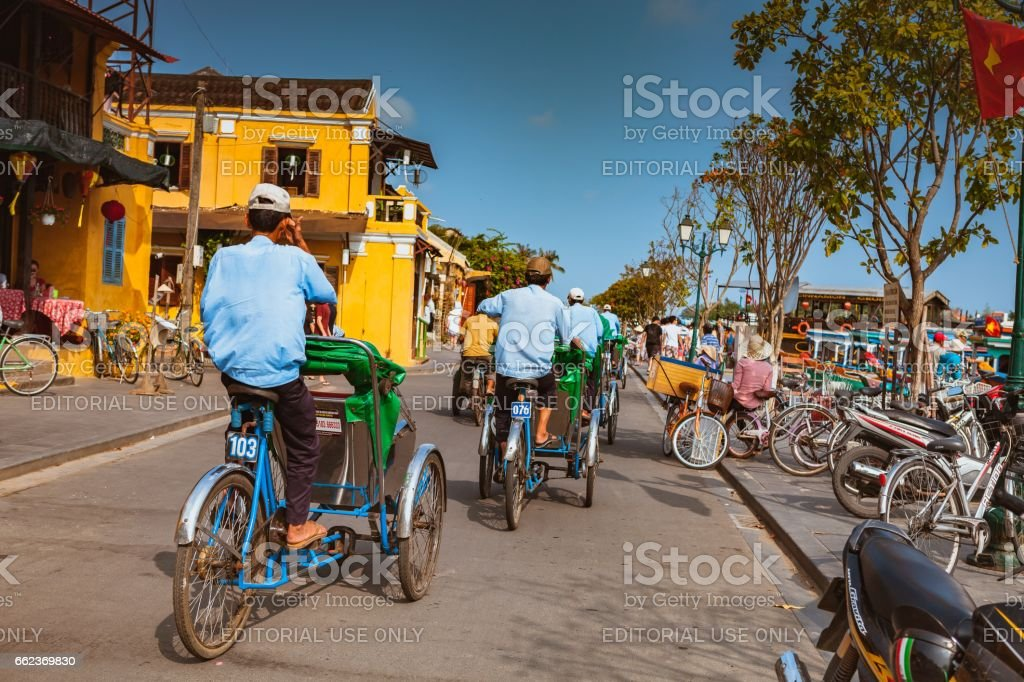HOI AN, VIETNAM - MARCH 15, 2017: local Vietnam man riding a traditional cycle in Hoi An. Hoi An, a UNESCO World Heritage site, is a major touristic destination in Central Vietnam stock photo