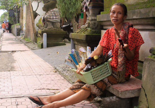 Local woman selling objects in Denpasar street stock photo