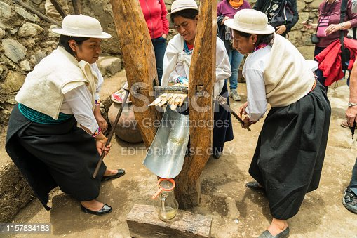 Alausi, Ecuador - March 2, 2019: Local women in traditional clothing pressing aloe juice for tourists at the train Nariz del Diablo railway station.