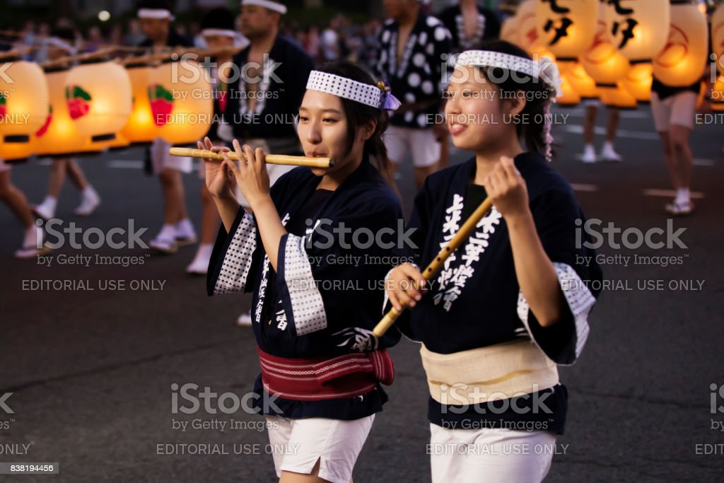 Local young ladies play Japanese transverse bamboo flute to make rhythm in festival stock photo