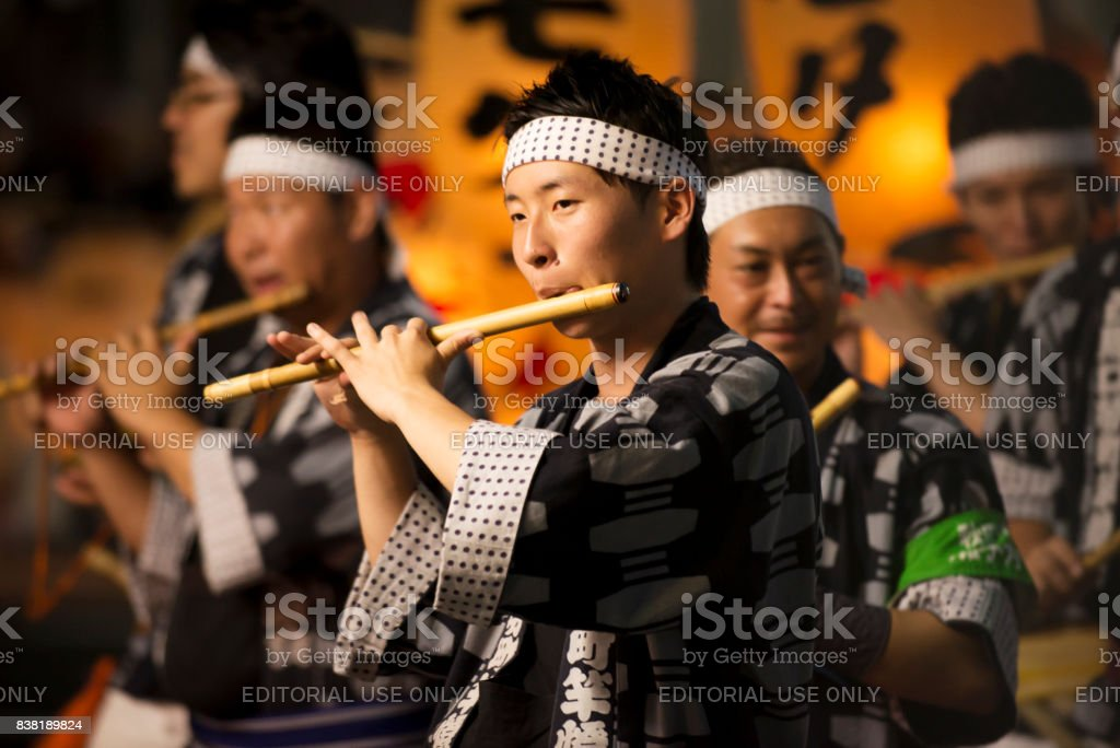 Local young men play Japanese transverse bamboo flute to make rhythm in festival stock photo
