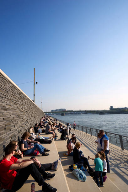 Locals and tourists alike are enjoying the early evening sunshine on the banks of the Rhine river at the base of the Hohenzollern Bridge stock photo