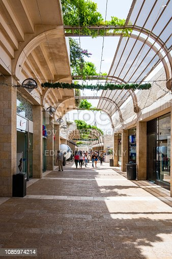 Jerusalem, Israel - May 25, 2012: Locals and tourists walking by the famous Mamilla street full of shops and bars partly covered with roof pergola arch with growing plants and flowers on it