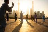 Shanghai, China - October 28, 2015: Local people performing Tai Chi in the early morning on the Bund with the Oriental Pearl TV Tower and skyscrapers of Pudong in the background.