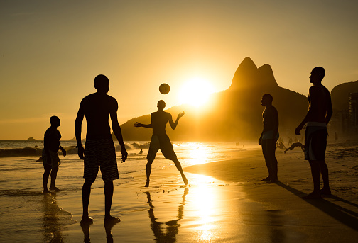 Rio de Janeiro, Brazil - February 05, 2016: Silhouette of locals playing ball at sunset in Ipanema beach, Rio de Janeiro, Brazil.