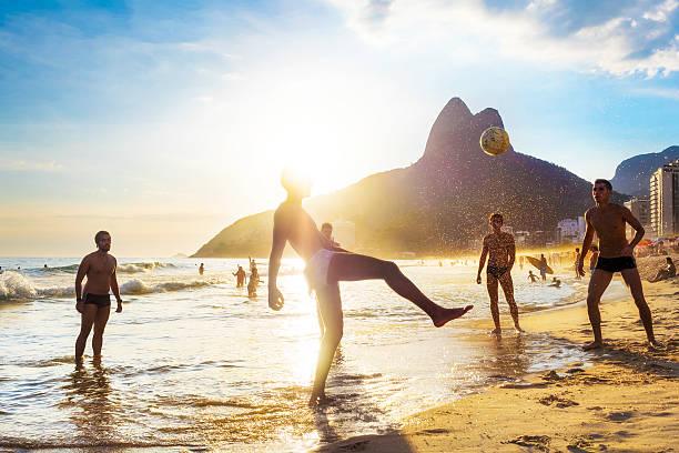 einheimische spielen ball in strand von ipanema, rio de janeiro, brasilien - rio de janeiro stock-fotos und bilder