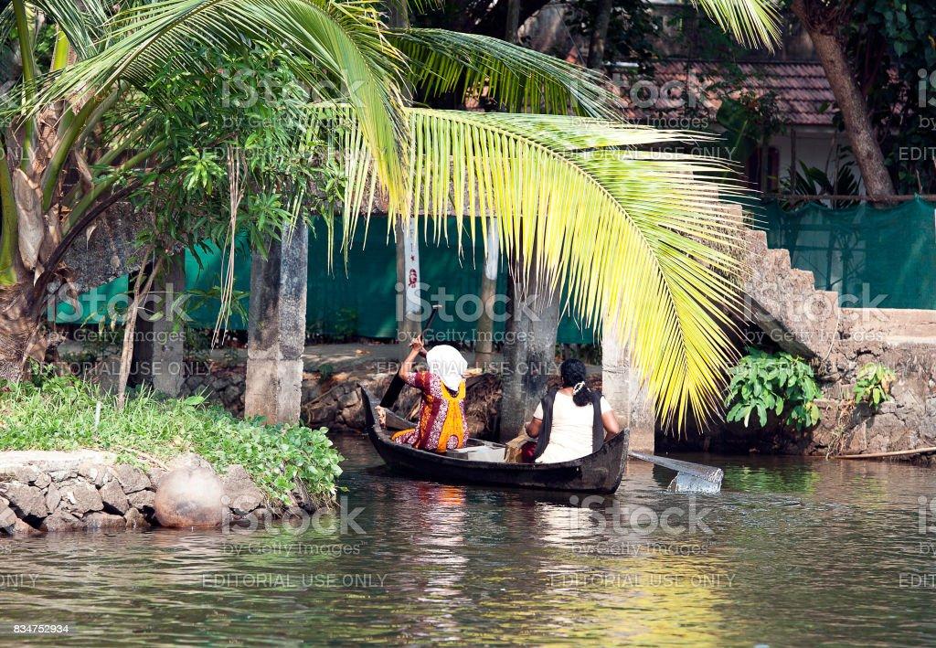 Locals rowing under bridge, Keralan backwater lagoon, Kumarakom, Kerala, Southern India. stock photo