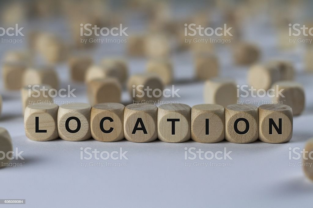 location - cube with letters, sign with wooden cubes stock photo