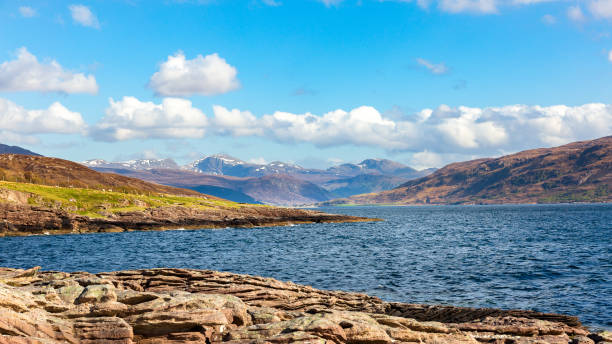 Loch Broom near Rhue with the mountain Beinn Dearg in the background Loch Broom near the village Rhue with the snowy mountains of Beinn Dearg in the background north coast 500 stock pictures, royalty-free photos & images
