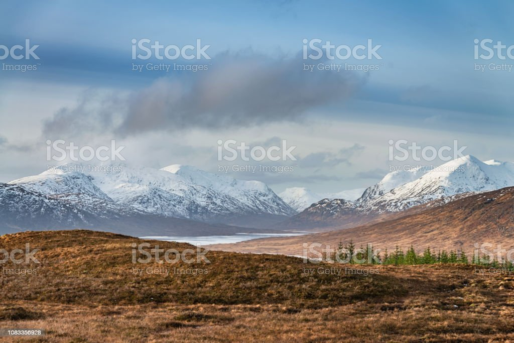 Loch Loyne Snowcapped Mountains Scottish Highlands Winter Scotland Majestic snowcapped Scotland Mountains in winter under beautiful blue sky. Loch Loyne in front of the Mountain Range. North West Scottish Highlands, Scotland, United Kingdom. Atmospheric Mood Stock Photo