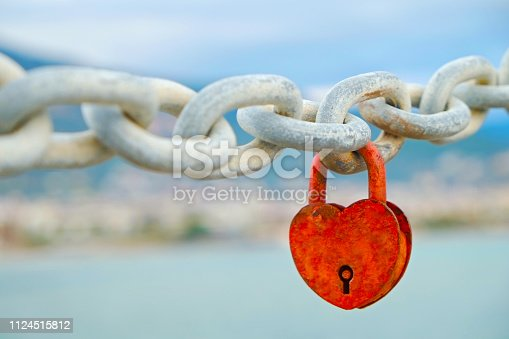 istock Lock in the form of heart hanging on chain over the sea view background. 1124515812