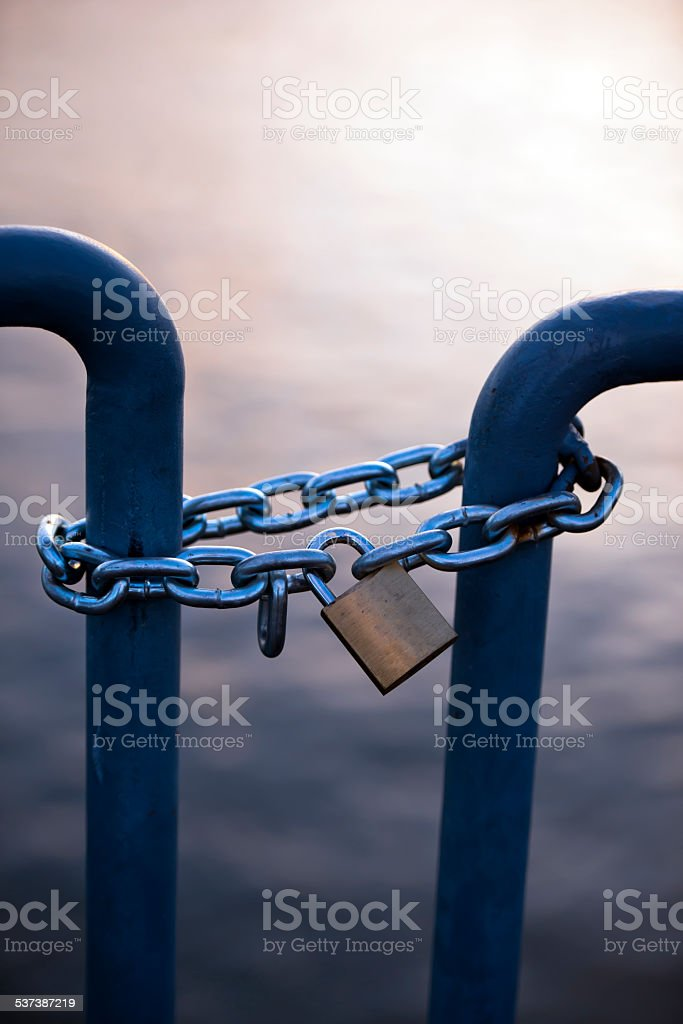 Lock on chain connecting barrage turnstile evening stock photo
