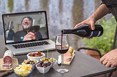 istock Lockdown aperitif video call party. Adult men are making a pre-meal aperitif with snacks, wine, and Italian appetizers together at home using teleconference platform apps during COVID-19 restrictions 1264266969