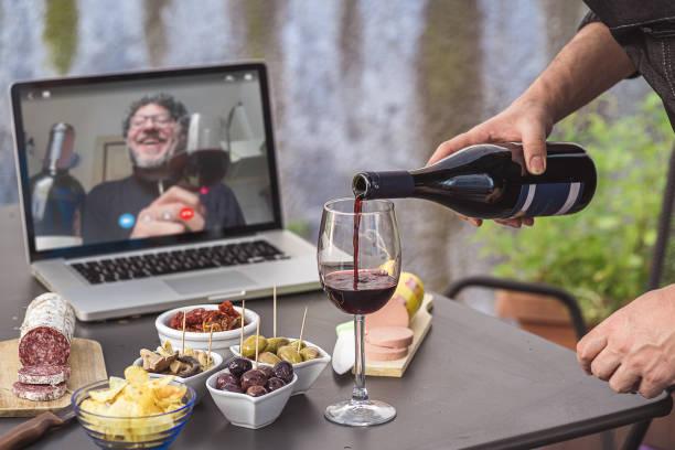 잠그기 아페리티프 화상 통화 파티. 성인 남성은 covid-19 제한 기간 동안 원격 회의 플랫폼 앱을 사용하여 집에서 스낵, 와인 및 이탈리아 전채와 함께 식사 전식대식을 만들고 있습니다. - 식전 반주 뉴스 사진 이미지