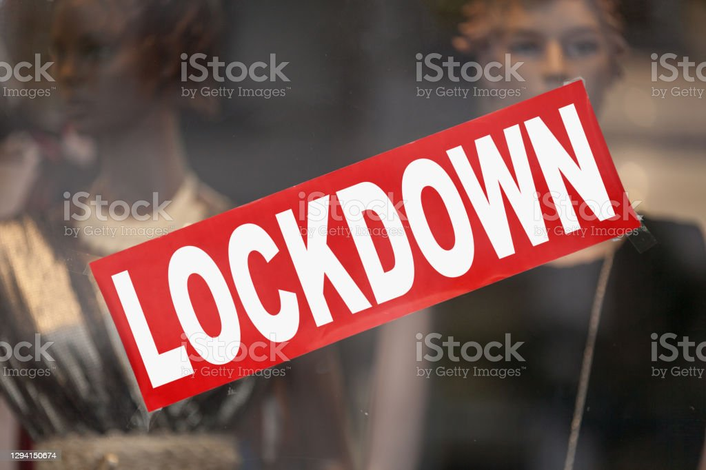 """Lockdown - Closed sign Red sign in a window shop saying in """"Lockdown"""". Bankruptcy Stock Photo"""