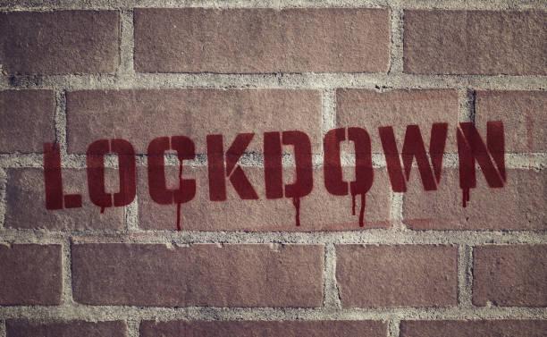 """Lockdown"" Stencil Spray-Painted on Brick Wall stock photo"