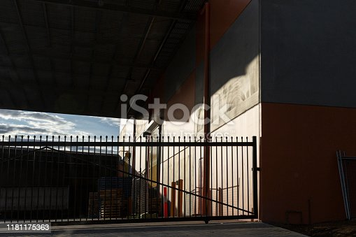 istock Locked Factory Facility Gate On Summers Afternoon 1181175363