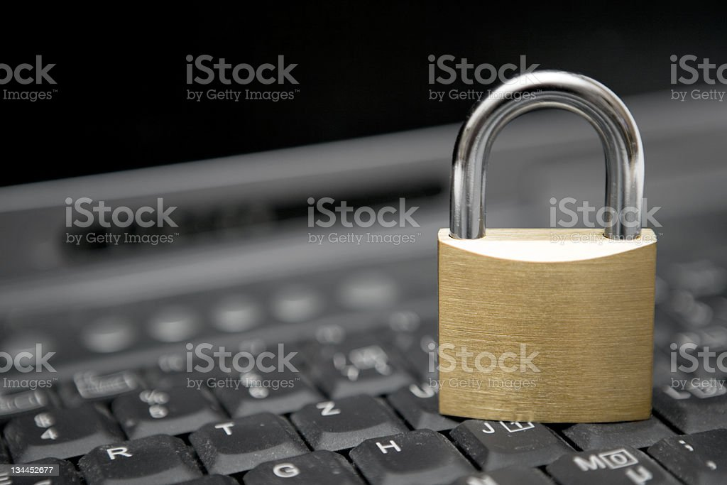 A locked padlock on top of a computer keyboard stock photo