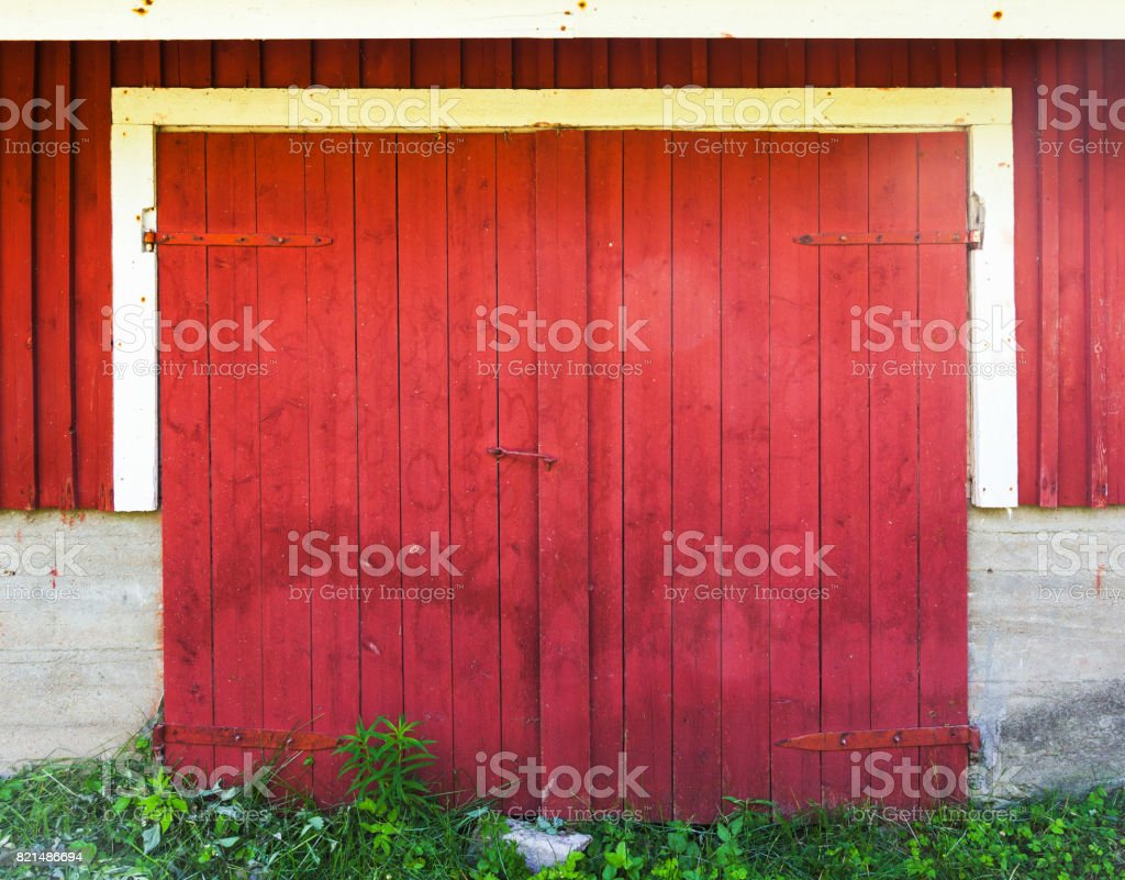 Locked red wooden gate in rural barn wall stock photo