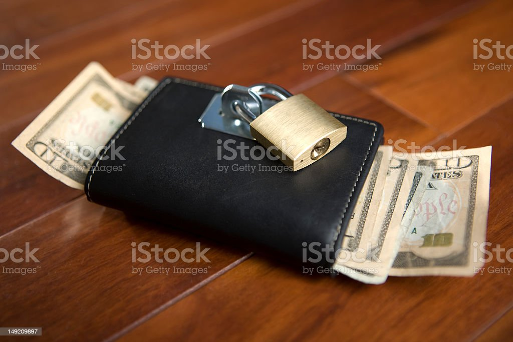 A padlock seals a wallet shut to keep from spending money in these...