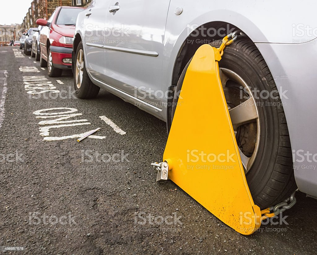 Locked wheel clamp on parked car stock photo