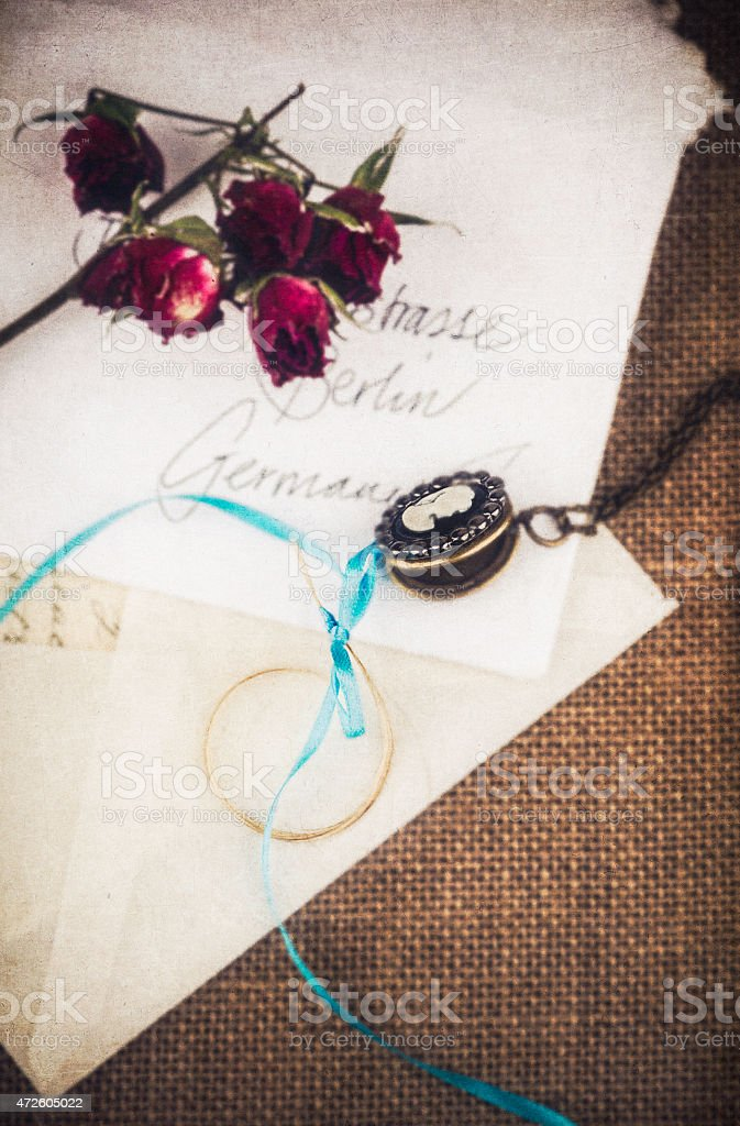Locket with love letter and dried roses. Nostalgia, memories, bygones stock photo