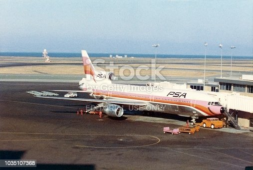 PSA (Pacific Southwest Airlines) Lockheed L-1011 TriStar jet airplane at gate at San Francisco International Airport, California, USA, August 1974. Scanned film with grain.
