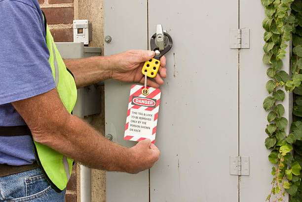 lockout tag man attaching a lockout tag to an electrical control panel lockout stock pictures, royalty-free photos & images