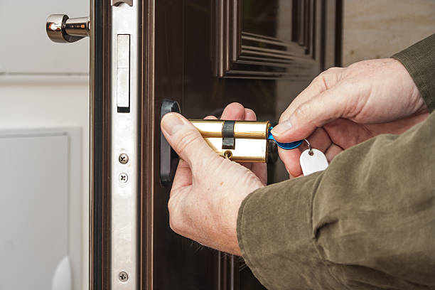 Locksmith replacing a cylinder lock Locksmith replacing a cylinder lock locksmith stock pictures, royalty-free photos & images