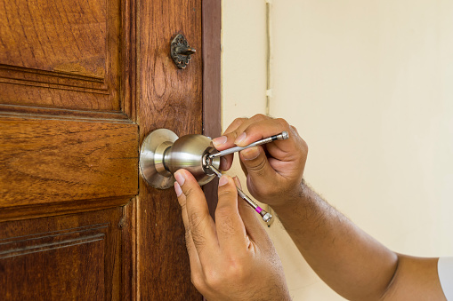 istock locksmith use screwdrive open wood door in emergency time 824733106