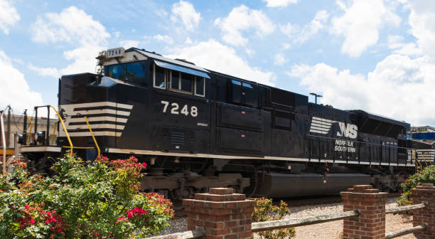 Locomotive passing train station Hickory, NC, USA-26 May 18: A Norfolk Southern locomotive pulls its cargo through a downtown area. southern usa stock pictures, royalty-free photos & images