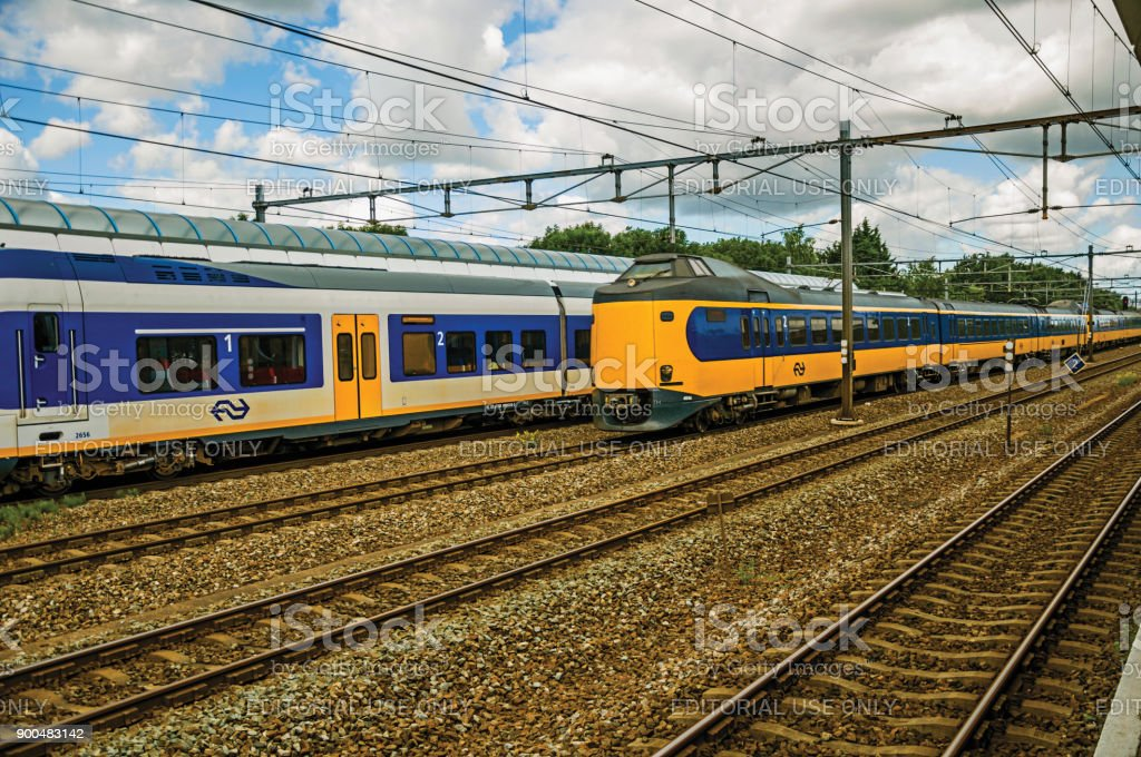 Locomotive stop on train station and other train passing by in cloudy day at Weesp. stock photo