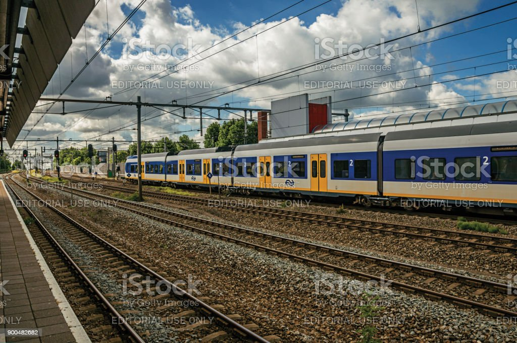 Locomotive stop on train station platform, railroad rails and blue cloudy sky at Weesp. stock photo