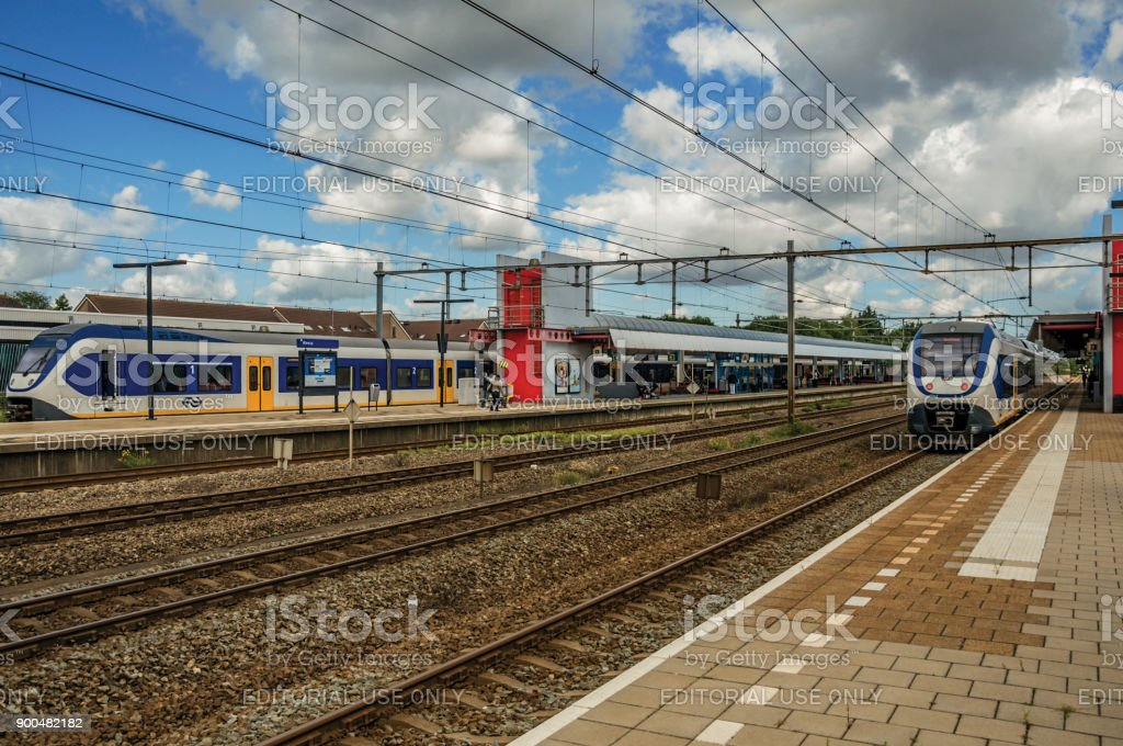 Locomotives stop on train station platforms, railroad rails and cloudy sky at Weesp. stock photo