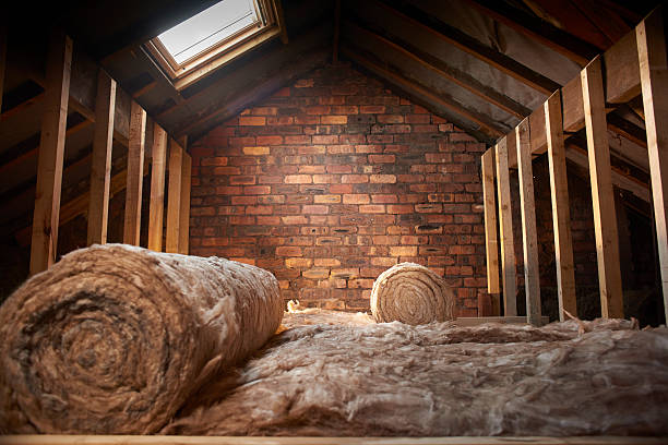 loft insulation rolls of insulation partially installed in a loft space. attic stock pictures, royalty-free photos & images