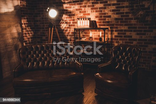 istock Loft interior. Leather couch and armchair in a dark room 944666344